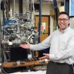 Brad Ferguson next to the molecular beam apparatus that he used as a graduate student during a visit to Austin in May 2015.